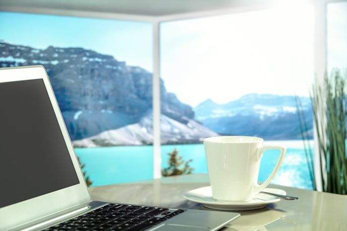notebook e xícara de café com paisagem no fundo