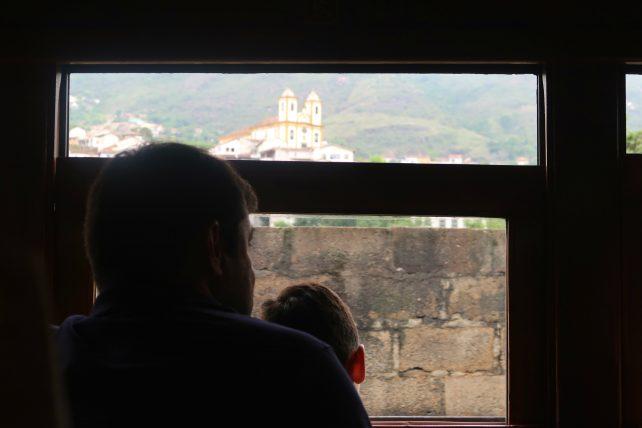 pai e filho olhando pela janela do trem