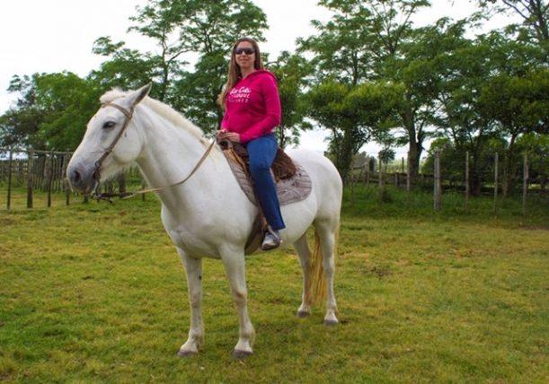mellina montada em um cavalo branco